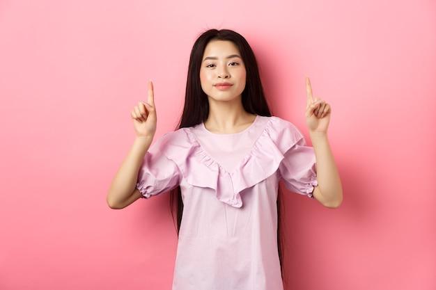 Uśmiechnięta nastolatka azjatka wskazując palcami w pustej przestrzeni, reklama na różowym tle.