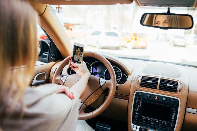 Uśmiechnięta nastolatka biorąc zdjęcie selfie aparatem smartphone na zewnątrz w samochodzie
