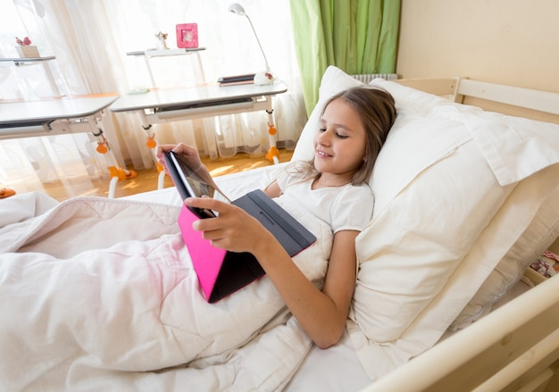 Uśmiechnięta nastolatka korzystająca z cyfrowego tabletu w łóżku