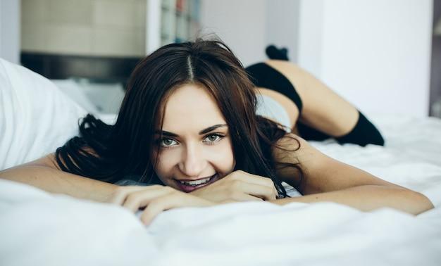 Uśmiechnięta nastolatka leżącego na łóżku