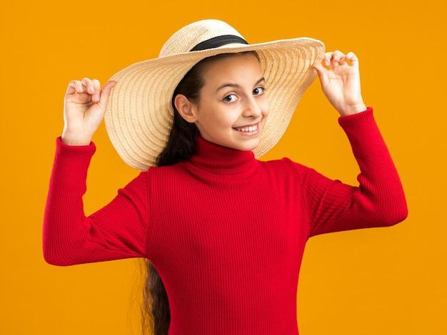 Uśmiechnięta nastolatka nosząca i chwytająca kapelusz plażowy odizolowana na pomarańczowej ścianie