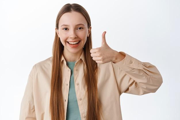 Uśmiechnięta nastolatka pokazuje kciuki do góry i mówi tak, kiwa głową z aprobatą, chwali doskonały wybór, poleca coś fajnego, stoi zadowolona na białej ścianie