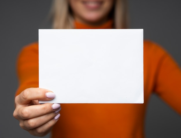 Uśmiechnięta nastolatka posiada makieta duży pusty arkusz papieru z miejscem na tekst.