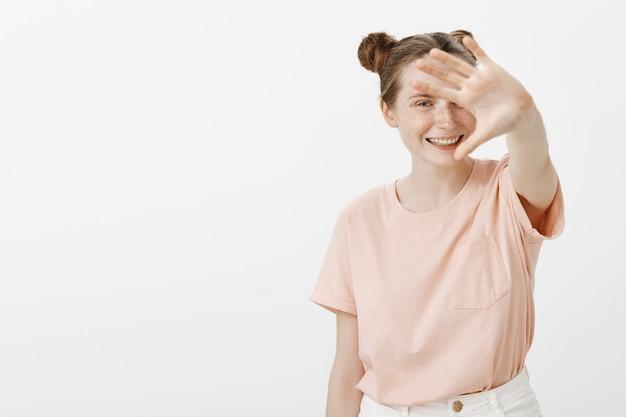 Uśmiechnięta nastolatka pozuje na białej ścianie