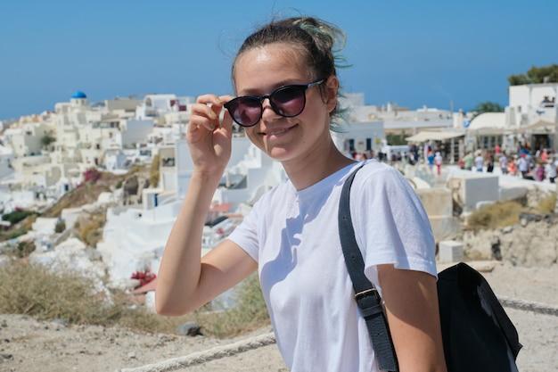 Uśmiechnięta nastolatka pozuje na wyspie santorini z oia w grecji