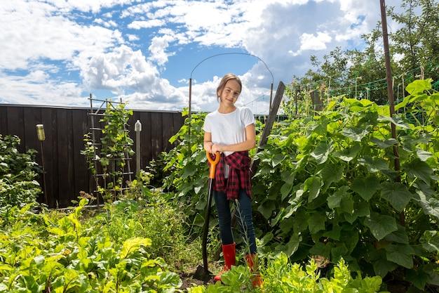 Uśmiechnięta nastolatka pracująca z łopatą w ogrodzie