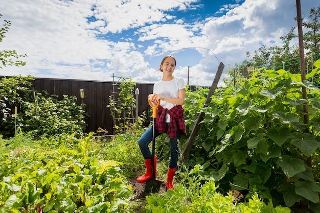 Uśmiechnięta nastolatka pracująca z łopatą w sadzie