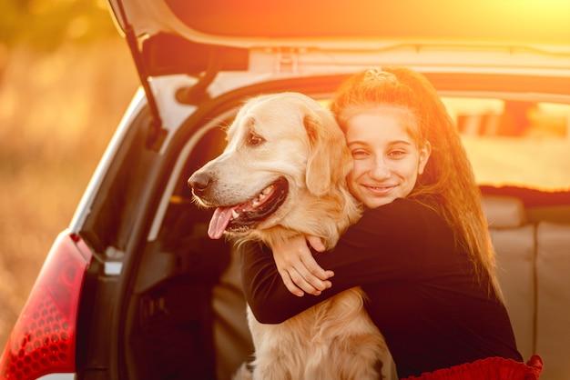 Uśmiechnięta nastolatka przytulająca psa golden retrievera w bagażniku samochodu pod słońcem