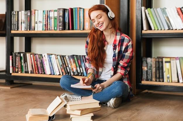 Uśmiechnięta nastolatka robi pracę domową
