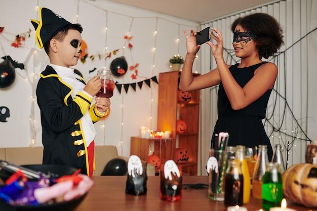 Uśmiechnięta nastolatka robi zdjęcie swojego młodszego brata w pirackim kostiumie na halloween na imprezie