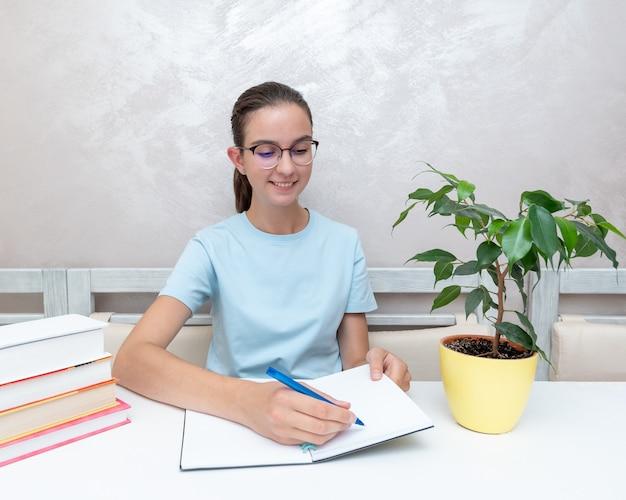 Uśmiechnięta nastolatka siedząca przy stole z książkami pisze zadanie w zeszycie. dziewczyna jest studentką studiującą o przyjęcie na uniwersytet, liceum. powrót do koncepcji szkoły.