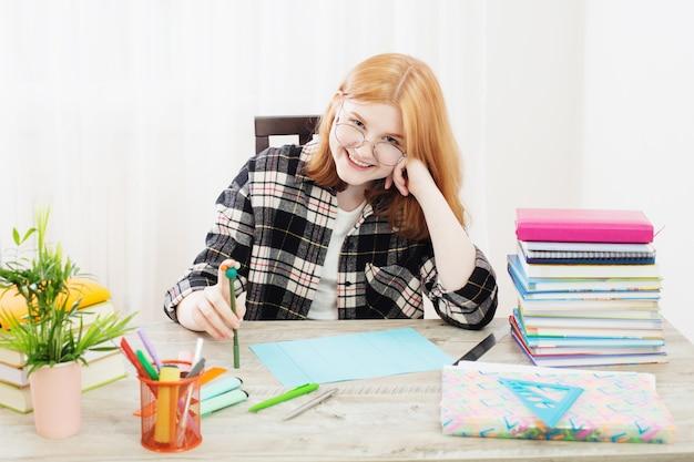 Uśmiechnięta nastolatka studentka w okularach odrabiania lekcji w domu koncepcja edukacji i szkoły