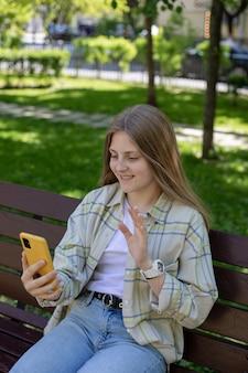 Uśmiechnięta nastolatka trzymająca smartfona robiąca selfie podczas wideorozmowy ze znajomymi