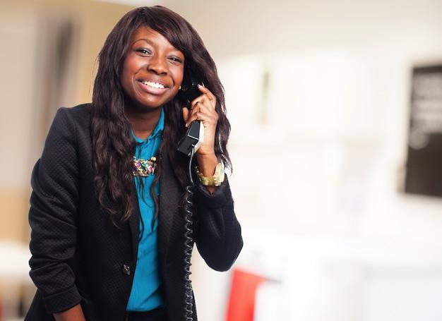 Uśmiechnięta nastolatka w garniturze rozmawia przez telefon