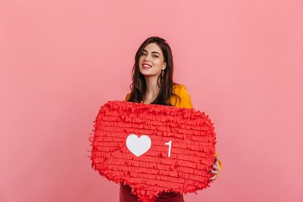"""Uśmiechnięta nastolatka w jasnym stroju trzyma na różowej ścianie czerwony znak """"like"""" z instagrama."""