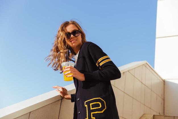 Uśmiechnięta nastoletnia dziewczyna pije sok pomarańczowego w okularach przeciwsłonecznych