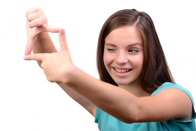 Uśmiechnięta nastoletnia dziewczyna robi ramie z jej palcami