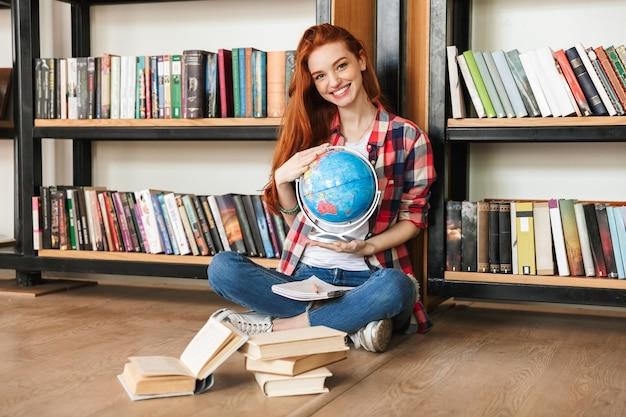 Uśmiechnięta nastoletnia dziewczyna trzyma kulę ziemską