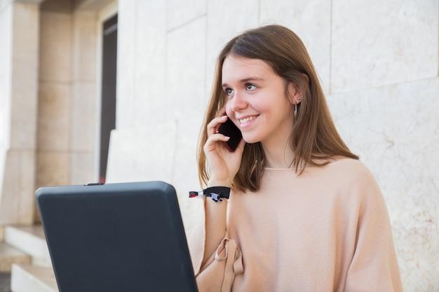Uśmiechnięta nastoletnia dziewczyna używa laptop i telefon przy budynek ścianą