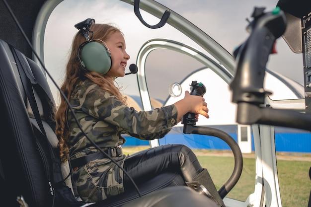 Uśmiechnięta nastoletnia dziewczyna w słuchawkach lotnika siedząca w kokpicie helikoptera