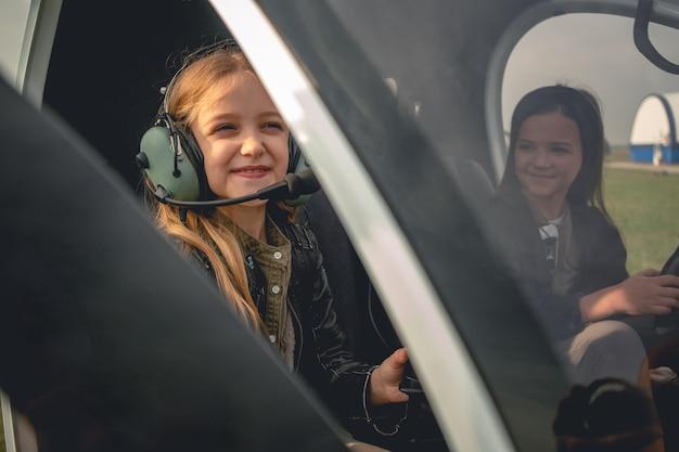 Uśmiechnięta nastoletnia dziewczyna w słuchawkach pilota siedząca w kokpicie helikoptera