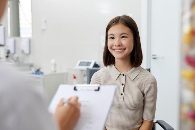 Uśmiechnięta nastoletnia kobieta w lekarkach biurowych