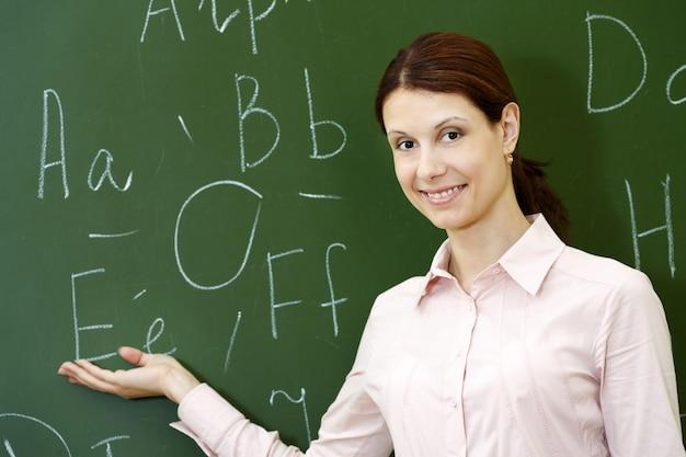 Uśmiechnięta nauczyciel z tablicą tle