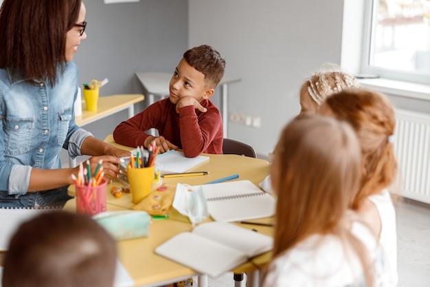 Uśmiechnięta nauczycielka ma lekcję z dziećmi w klasie