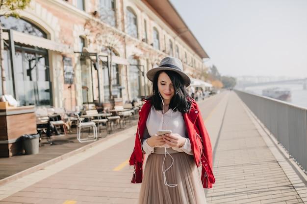 Uśmiechnięta nieśmiała kobieta w kapeluszu stojąc na ulicy i patrząc na telefon