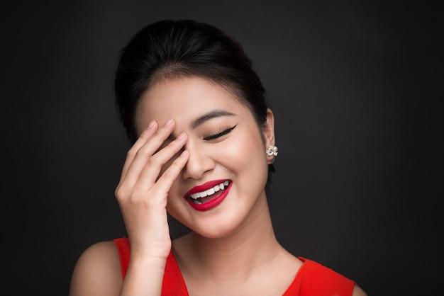 Uśmiechnięta nieśmiała kobieta zamknęła twarz ręką na czarnym tle.