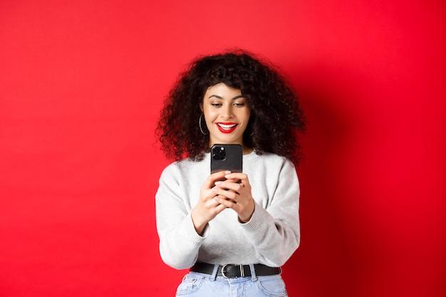 Uśmiechnięta nowoczesna dziewczyna robiąca zdjęcia na smartfonie, patrząca na ekran i nagrywająca wideo, stojąca na czerwonym tle
