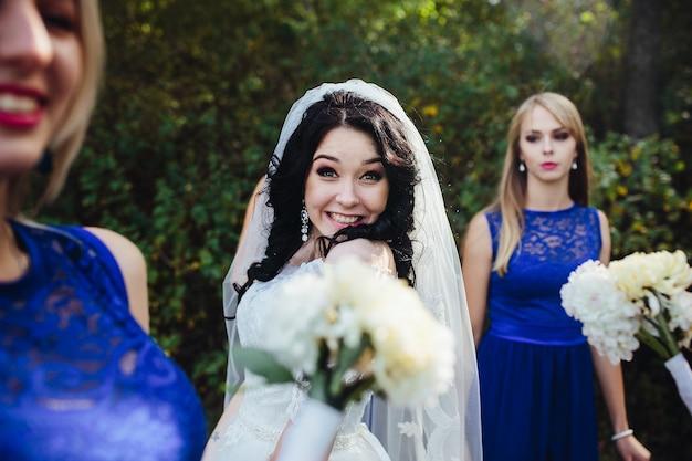 Uśmiechnięta oblubienica spojrzenie na aparat fotograficzny stwarzających