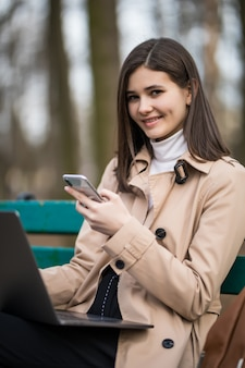 Uśmiechnięta oferta modela dziewczyna pracuje na laptopie i telefonie outside w parku