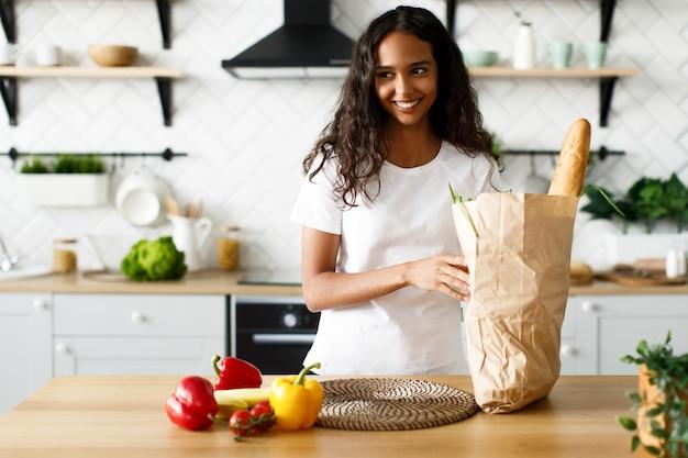 Uśmiechnięta oliwkowa kobieta trzyma paczkę z bagietką i warzywami w nowoczesnej białej kuchni