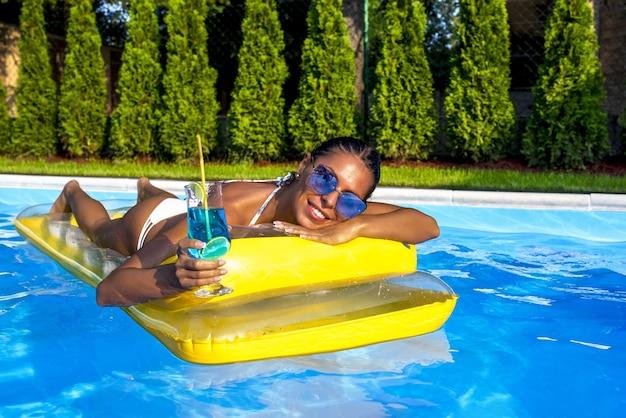 Uśmiechnięta opalona kobieta w bikini relaksuje się i pije koktajl na basenie