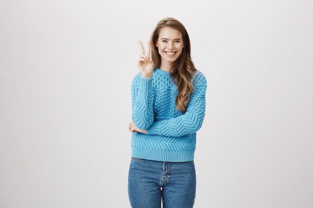 Uśmiechnięta optymistyczna kobieta pokazuje znak pokoju