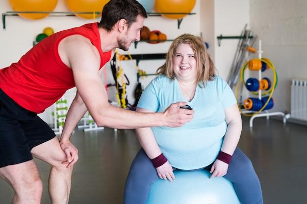 Uśmiechnięta otyła kobieta z trenerem