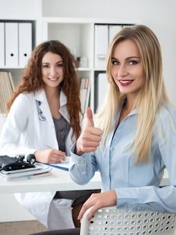 Uśmiechnięta pacjentka pokazuje znak ok z kciukiem do góry siedzi w gabinecie lekarskim. koncepcja usług medycznych na wysokim poziomie i jakości. najlepsza koncepcja leczenia i opieki nad pacjentem