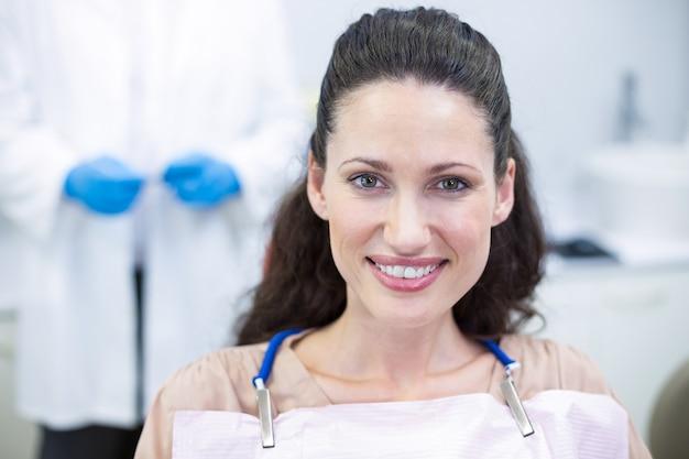 Uśmiechnięta pacjentka siedząca na krześle u dentysty
