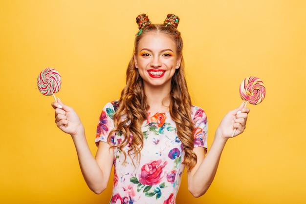 Uśmiechnięta pani trzymająca dwa ogromne kolorowe lizaki
