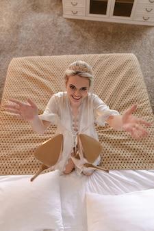 Uśmiechnięta panna młoda blondynka w pokoju hotelowym rzuca buty na łóżko