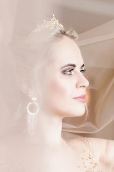 Uśmiechnięta panna młoda blondynka w pokoju hotelowym z koroną i welonem