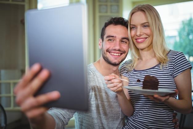 Uśmiechnięta para biorąc autoportretów z cyfrowym tablecie