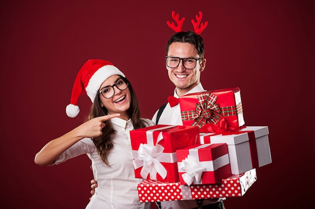 Uśmiechnięta para frajerów pokazuje prezent na boże narodzenie
