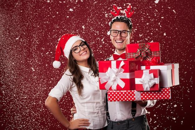 Uśmiechnięta para frajerów z dużą ilością świątecznych prezentów podczas śniegu
