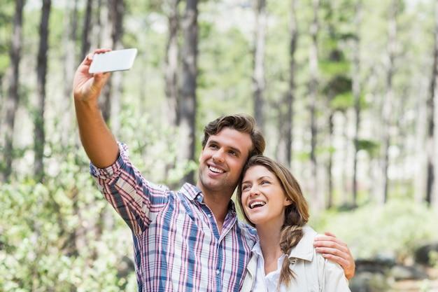 Uśmiechnięta para klika selfie z mądrze telefonem