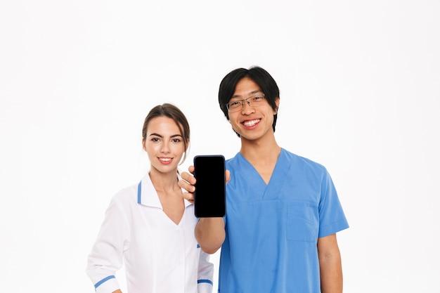 Uśmiechnięta para lekarzy na sobie jednolite stojących na białym tle nad białą ścianą, pokazując pusty ekran telefonu komórkowego