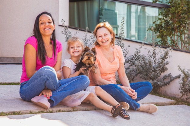 Uśmiechnięta para lesbijek z dzieckiem i zwierzęciem domowym szczeniakiem. para lesbijek gospodarstwa z ich przybraną córką, koncepcja przyjęcia.