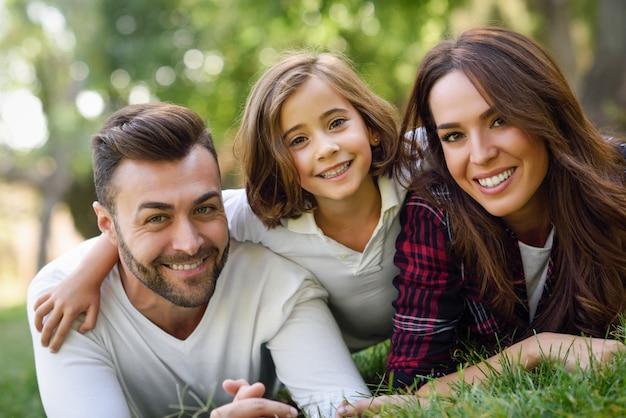 Uśmiechnięta para leżącego na trawniku z córką