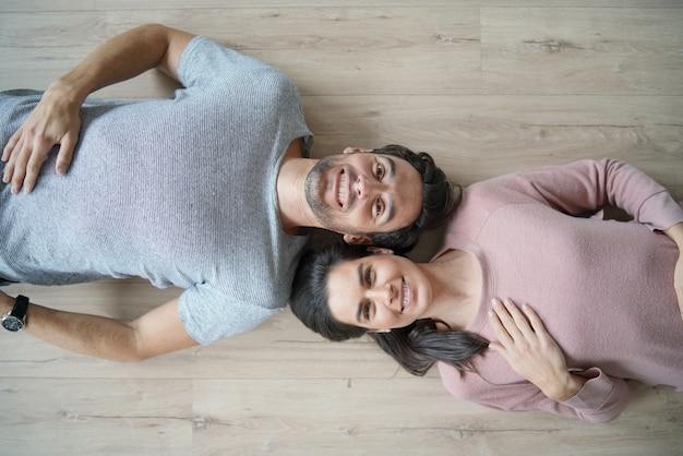 Uśmiechnięta para leży na drewnianej podłodze patrząc na kamery